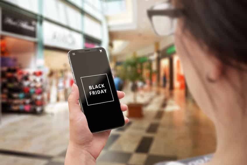 Woman use mobile phone for search for Black friday discounts. Black friday text on modern smartphone.